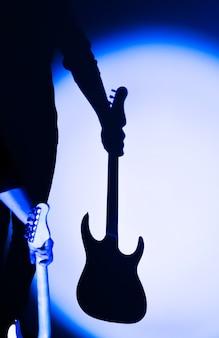 그림자에 일렉트릭 기타의 실루엣입니다. 악기를 들고 남자입니다. 스포트라이트를 받는 뮤지션. 밝은 그림자가 있는 창의적인 스타일.