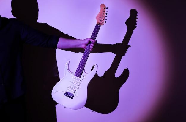 影の上のエレキギターのシルエット。楽器を持っている男。脚光を浴びているミュージシャン。明るい影のクリエイティブなスタイル。