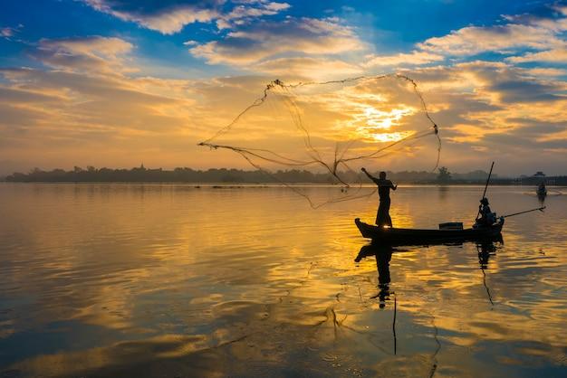早朝にネットを投げる漁師のシルエット