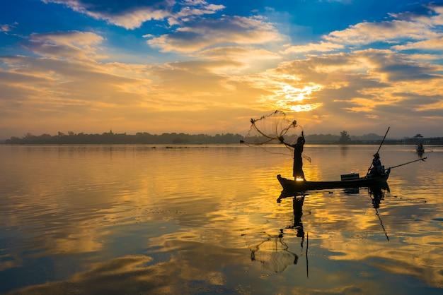湖に網を投げる漁師のシルエット