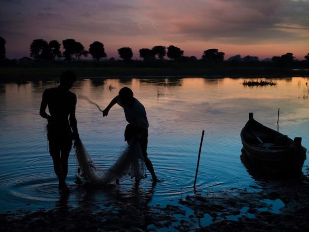 U bein橋、アマラプラ、マンダレー地域、ミャンマーの近くのボートで地元の漁師のシルエット。