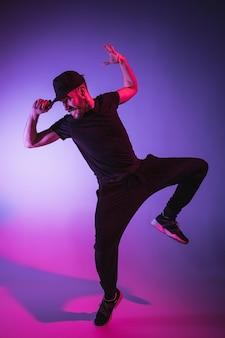 カラフルな背景で踊る1人の若いヒップホップ男性ブレイクダンサーのシルエット
