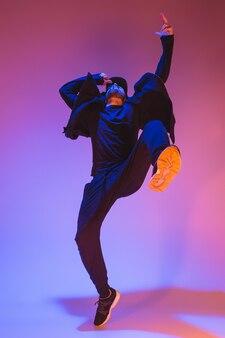 화려한 배경에서 춤을 추는 한 젊은 힙합 남성 브레이크 댄서의 실루엣