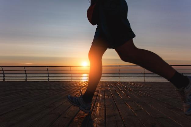 夜明けに海を駆け抜ける男性の脚のシルエット