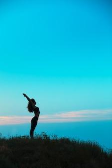 若い女性のシルエットはヨガを練習しています。