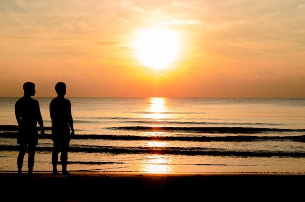 同性愛者のカップルがビーチで一緒に立っているのシルエット写真。