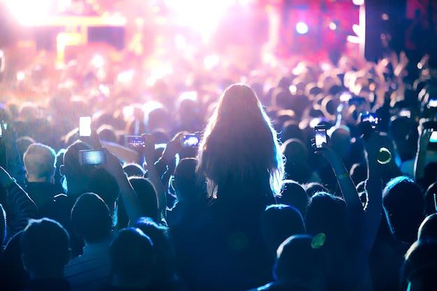 明るい舞台照明の前でコンサートの群衆のシルエット。抽象的なロックバンドのコンサート