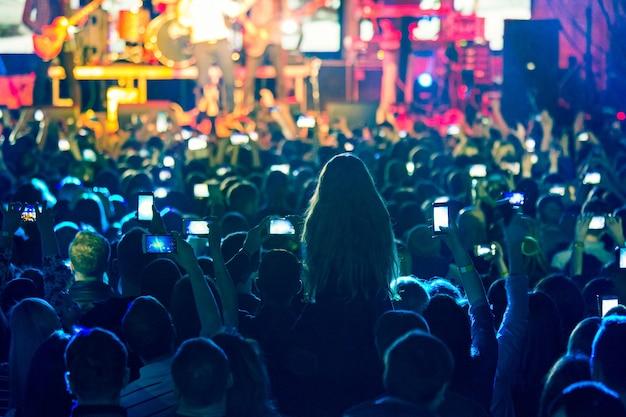 밝은 무대 조명 앞에서 콘서트 관중의 실루엣. 추상 록 밴드의 콘서트