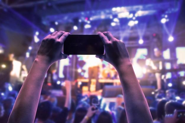 밝은 무대 조명 앞에서 콘서트 관중의 실루엣. 추상 록 밴드의 콘서트 프리미엄 사진