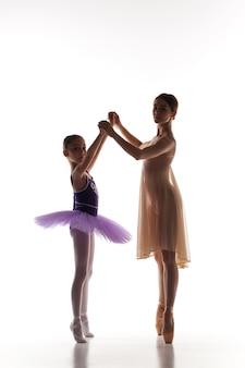 흰색 배경에서 춤을 추는 댄스 스튜디오에서 작은 발레리나와 개인 클래식 발레 교사의 실루엣