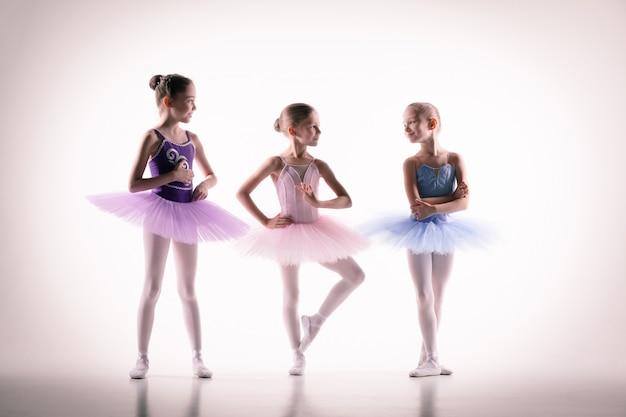 흰색 배경에 포즈를 취하는 댄스 스튜디오에서 작은 발레리나의 실루엣