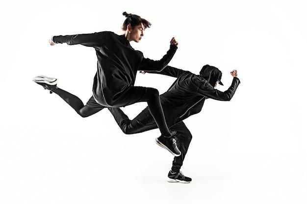 白いスタジオの背景で踊る2人の若いヒップホップの男性と女性のブレイクダンサーのシルエット