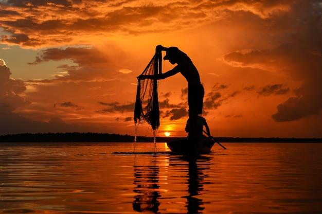 日の出、タイの中に川のsilluate漁師のボート