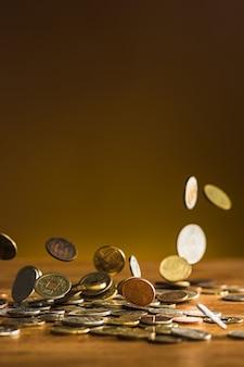Серебряные и золотые монеты и падающие монеты на деревянном фоне