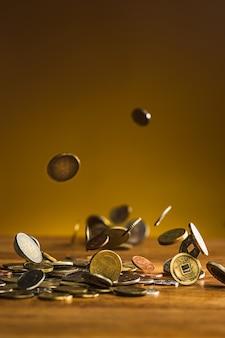 銀と金のコインと木製の背景に落ちるコイン