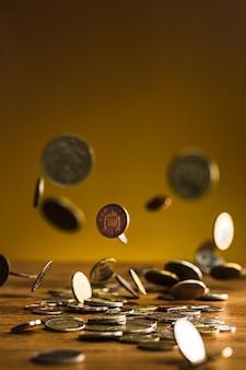 나무 벽에 은색과 황금 동전과 떨어지는 동전