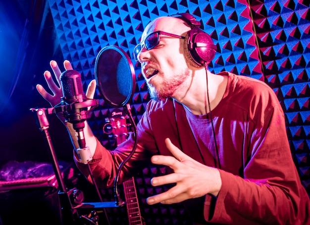 Певица поет с микрофоном в студии звукозаписи.