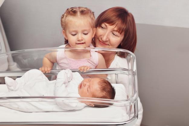 姉と祖母が病棟で生まれたばかりの赤ちゃんを見ている