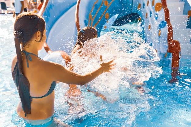Сестра ловит свою младшую сестру, которая скатывается с горки прямо в бассейн.