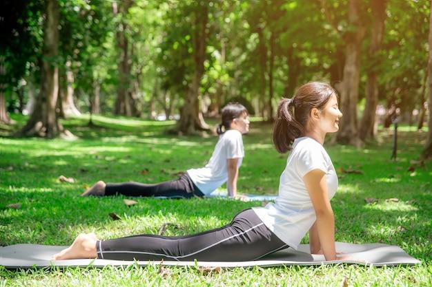 Сестры в белых практикуют медитацию в парке утром.