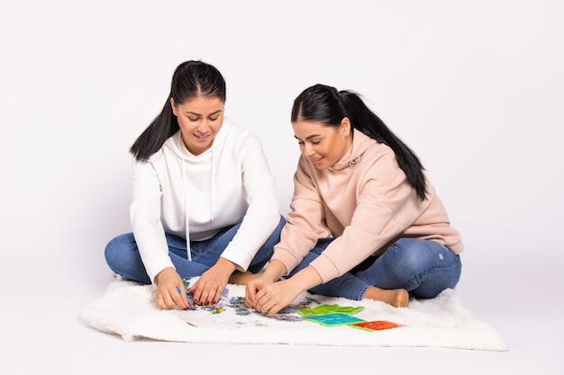 집에서 바닥에 앉아있는 자매들은 다리를 꼬고 퍼즐을 맞추 었습니다.
