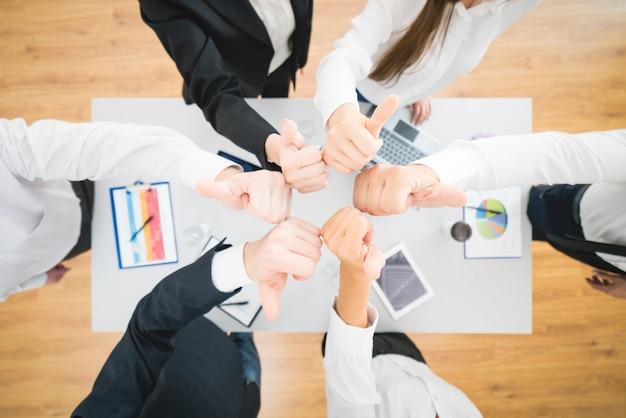 Сидящие деловые люди поднимают палец возле рабочего стола. вид сверху