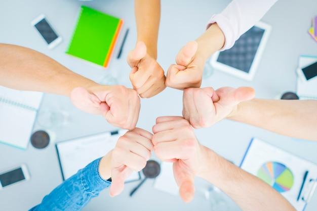 Шесть человек показывают пальцем вверх по столу. вид сверху