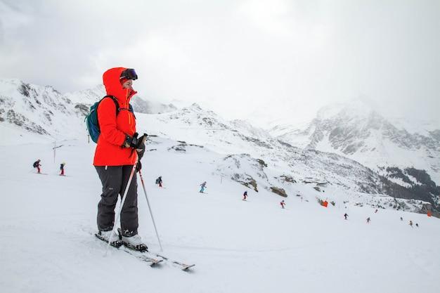 Лыжник стоит на склоне перед спуском и наблюдает за тренировкой лыжников