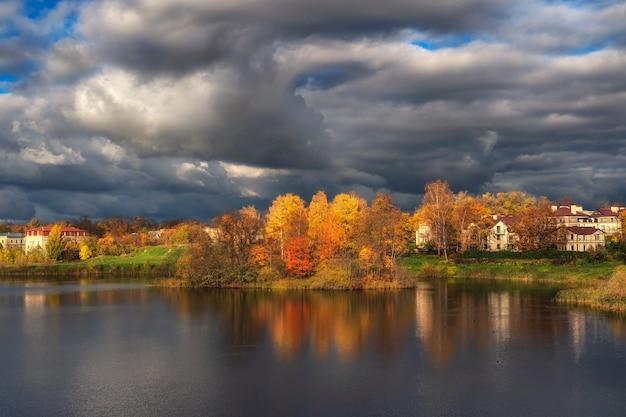 嵐の前の空。雷雨の前に湖の岸にある村の明るい秋の劇的な景色。