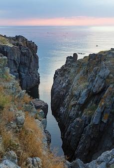 昇る朝日に照らされる空と岩壁からの海景。ボートに乗っている人は見分けがつきません。