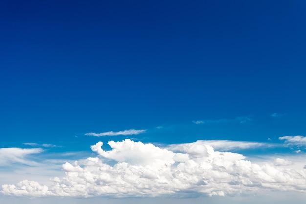 В ясный день небо голубое с белыми облаками.