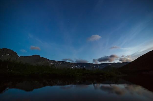 山の湖の水に映る夜明けの星空