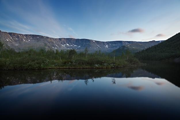 山の湖の水に映る夜明けの星のある空