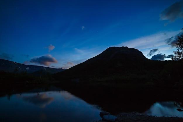 山の湖の水に映る、夜明けの星のある空。