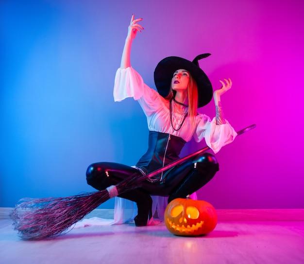 Стройная девушка в костюме ведьмы на хэллоуин с веником и тыквой