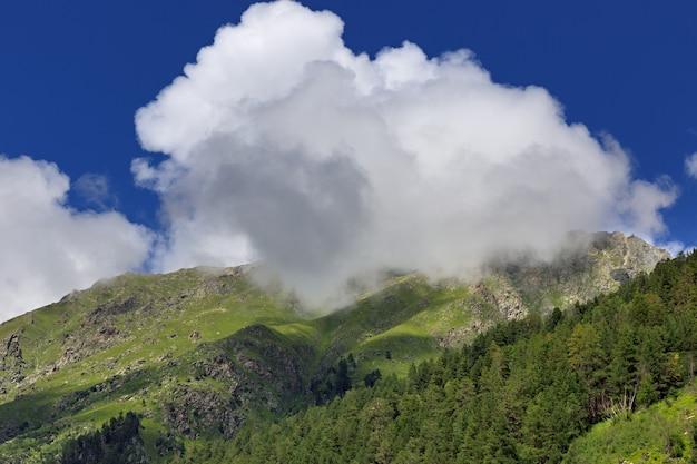 植生のある山の斜面は雲に隠れています。コーカサス山脈の高地地域の天候の変化。