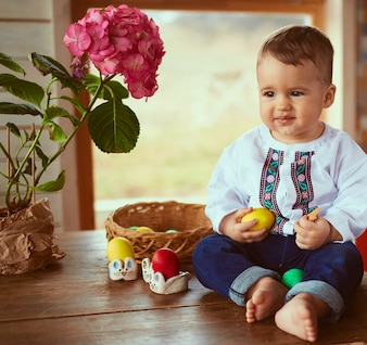 The small baby keeps a yellow egg and sits on the table
