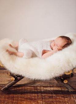 작은 아기가 바구니에 놓여 있습니다.
