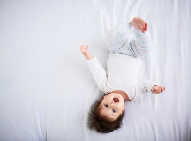 Маленький ребенок лежит на кровати