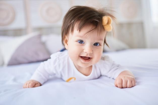 小さな赤ちゃんがベッドの上に横たわっている