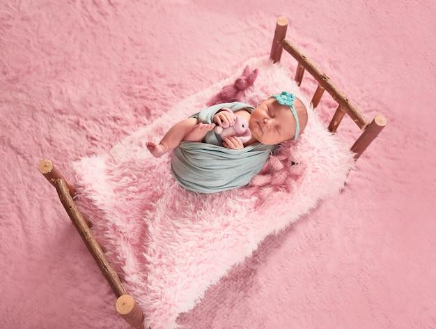 작은 아이는 장난감으로 침대에 누워