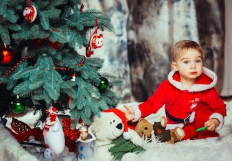 The small child sitting near Christmas tree