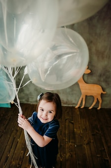 Маленькая девочка держит баллоны в комнате