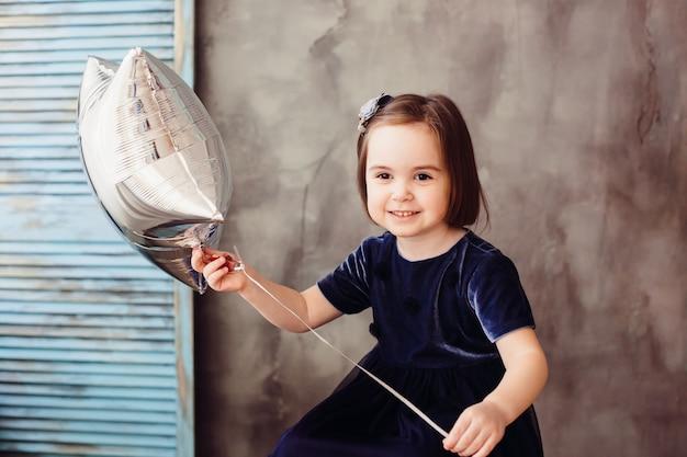 Маленькая девочка держит звезду и сидит на лестнице