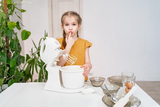 Маленькая девочка готовит тесто или крем в погружной миксере и облизывает пальцы. современная бытовая техника удобна и проста даже для детей. увлечение кулинарией. отпуск.