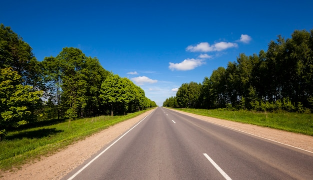 Небольшая сельская асфальтированная дорога в летнее время года. беларусь