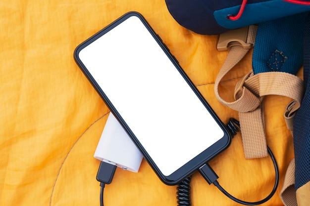 스마트 폰이 휴대용 충전기로 충전 중입니다. 배낭과 함께 침낭에 휴대 전화의 흰색 화면 모형이있는 전원 은행.