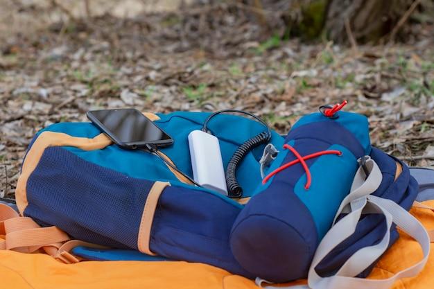 Смартфон заряжается с помощью портативного зарядного устройства. пауэрбанк с мобильным телефоном на спальнике с рюкзаком.