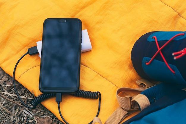 스마트폰이 휴대용 충전기로 충전되고 있습니다. 배낭이 달린 침낭에 휴대폰이 있는 보조 배터리.