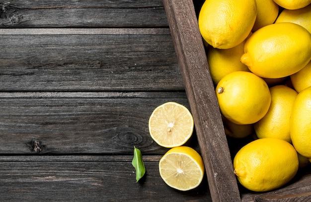 木箱に入ったフレッシュレモンの香り。黒い木製の背景に